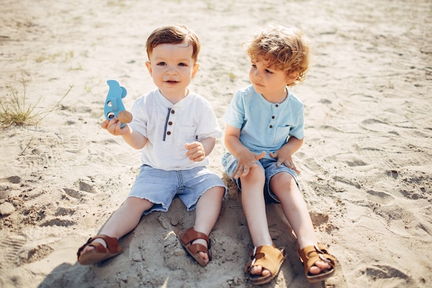 Mignons petits enfants jouant sur un sable