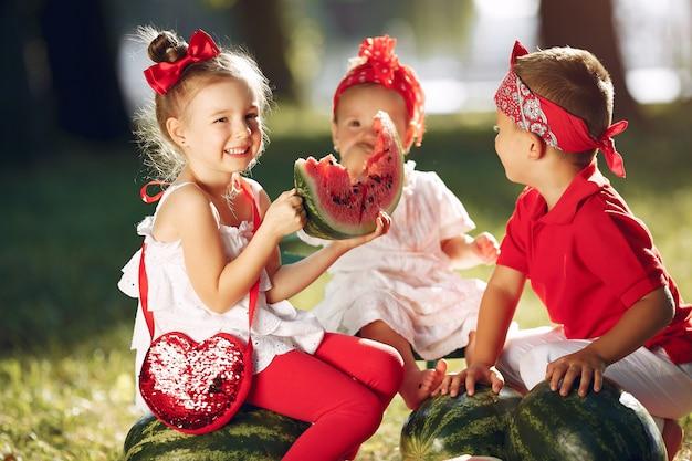 Mignons petits enfants avec des pastèques dans un parc