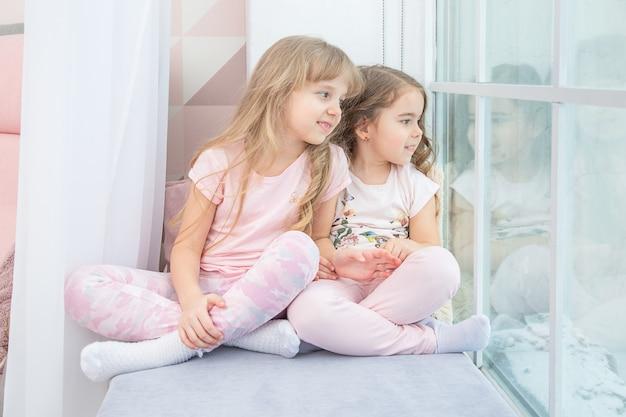 Mignons petits frères et sœurs assis sur le rebord de la fenêtre à la maison regarde par la fenêtre sur la neige, portrait de jolies petites filles sur le rebord de la chambre en hiver. adorable enfant pensif en rose, mignon bambin pendant la contemplation.