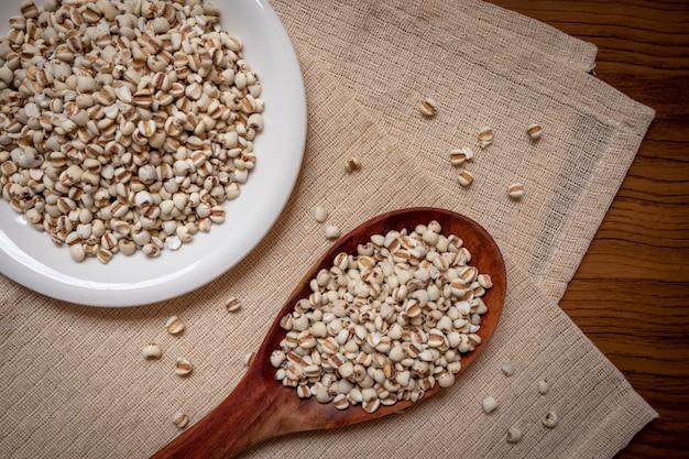 Mil dans une cuillère en bois qui est des céréales et de la nourriture sur une nappe brune