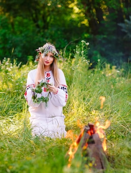 Milieu de l'été. femme tissant une couronne près du feu.