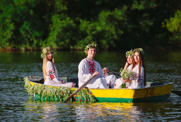 Milieu de l'été. un groupe de jeunes en costumes nationaux navigue dans un bateau orné de feuilles et de phanères. fête slave d'ivan kupala.