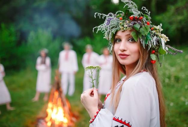 Milieu de l'été. portrait d'une belle fille en vêtements slaves près du feu.