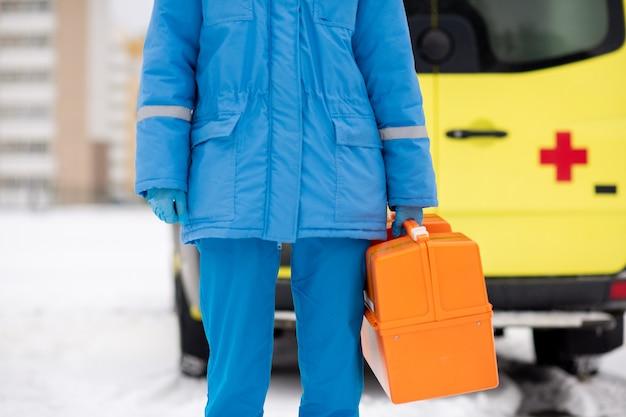 Milieu de la jeune ambulancier contemporain en vêtements de travail bleus et gants tenant une trousse de premiers soins en position debout