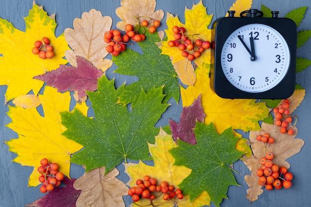 Milieu de la nuit d'halloween. horloge noire sur fond de feuilles colorées et de baies oranges, espace de copie. carte de joyeux halloween. il est temps de célébrer halloween