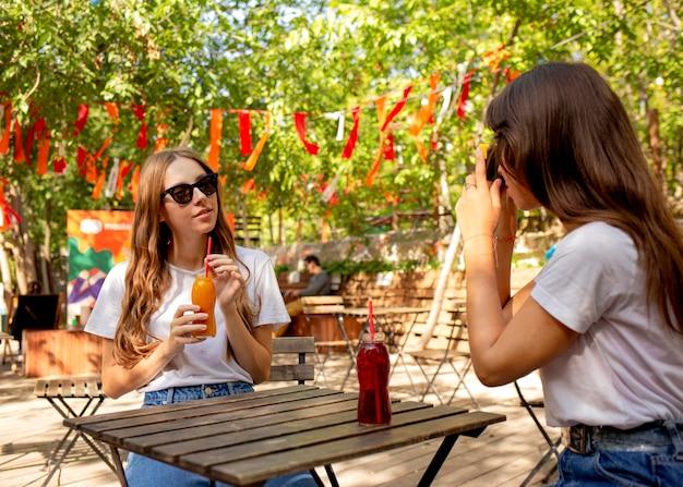 Milieu shot amis tenant des bouteilles de jus de fruits frais et prendre des photos