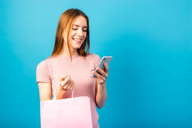 Milieu tir femme tenant sac et regarder téléphone