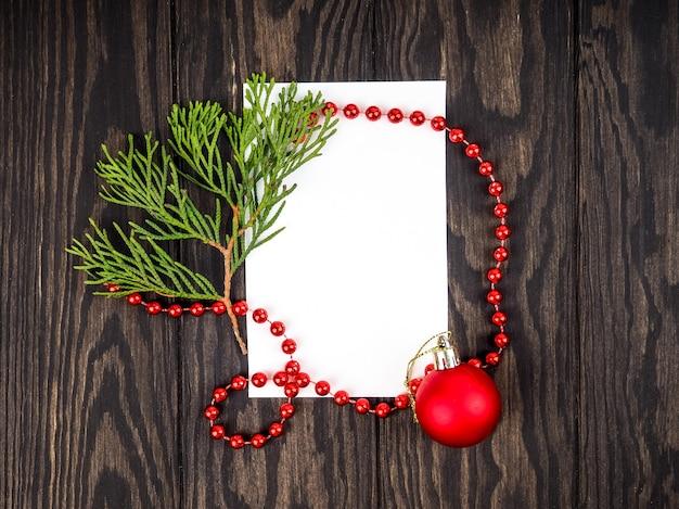 Milieux d'arbre de noël, mise en page créative faite de branches d'arbres de noël avec de la neige et une note de carte en papier. mise à plat. concept nature nouvel an.