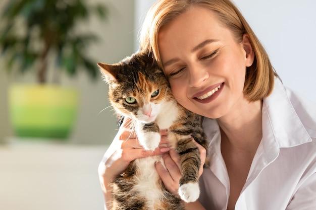 Miling femme en chemise blanche étreignant et embrassant avec tendresse et amour chat domestique à la maison