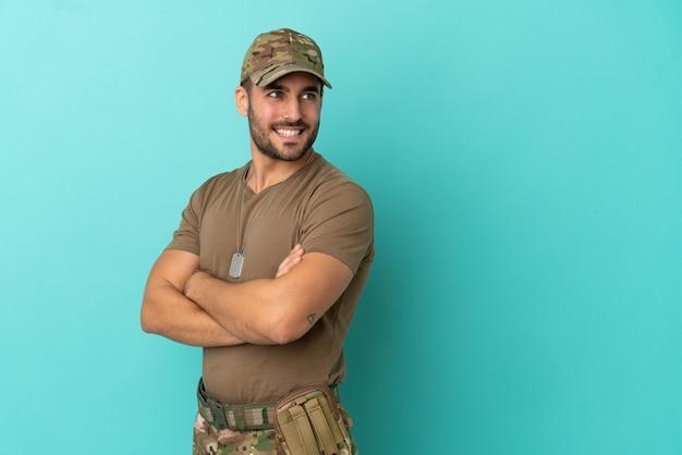 Militaire avec dog tag sur isolé sur fond bleu avec les bras croisés et heureux