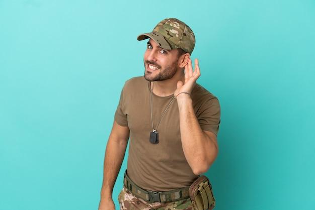 Militaire avec dog tag sur isolé sur fond bleu écoutant quelque chose en mettant la main sur l'oreille