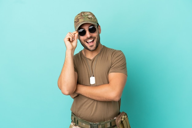 Militaire avec dog tag sur isolé sur fond bleu avec des lunettes et heureux