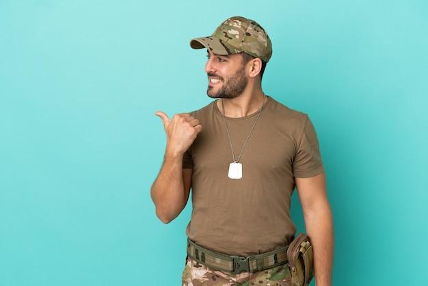Militaire avec dog tag sur isolé sur fond bleu pointant vers le côté pour présenter un produit