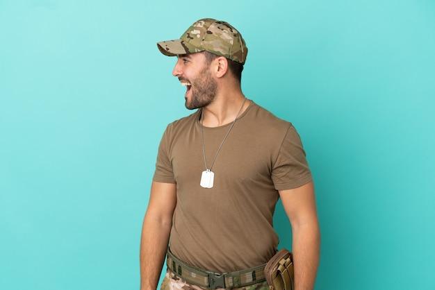 Militaire avec dog tag sur isolé sur fond bleu en riant en position latérale