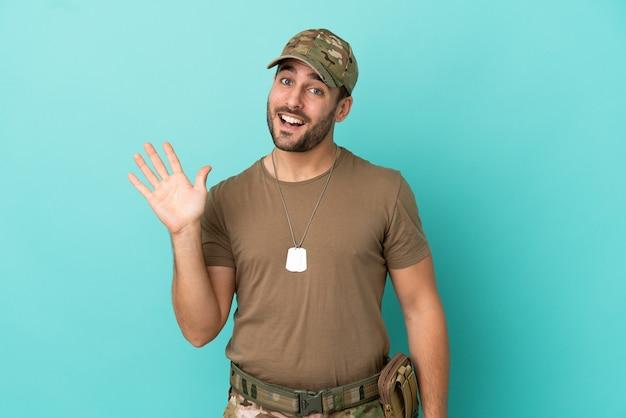 Militaire avec dog tag sur isolé sur fond bleu saluant avec la main avec une expression heureuse