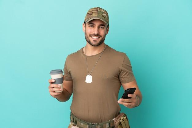 Militaire avec dog tag sur isolé sur fond bleu tenant du café à emporter et un mobile