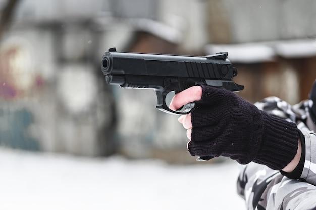 Un militaire avec un pistolet à côté de vieux bâtiments