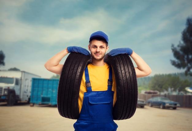 Un militaire en uniforme tient les pneus dans les mains. réparateur, montage de roues, service de pneus