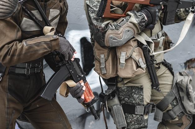 Les militaires avec des mitrailleuses effectuent la tâche en hiver.