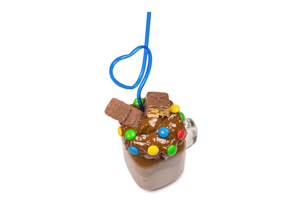 Milk-shake au chocolat avec crème fouettée, biscuits, gaufres, servi dans un bocal en verre.