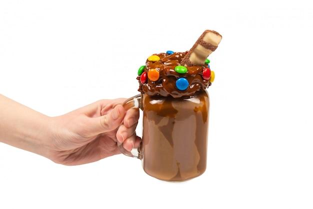 Milk-shake au chocolat avec crème fouettée, biscuits, gaufres, servi dans un bocal en verre mason