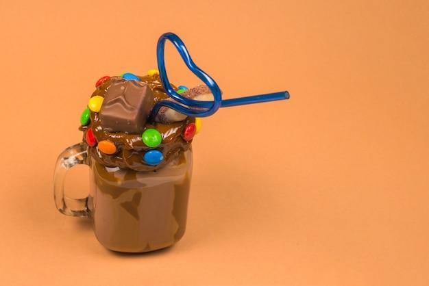 Milk-shake au chocolat avec crème fouettée, biscuits, gaufres, servi dans un bocal en verre