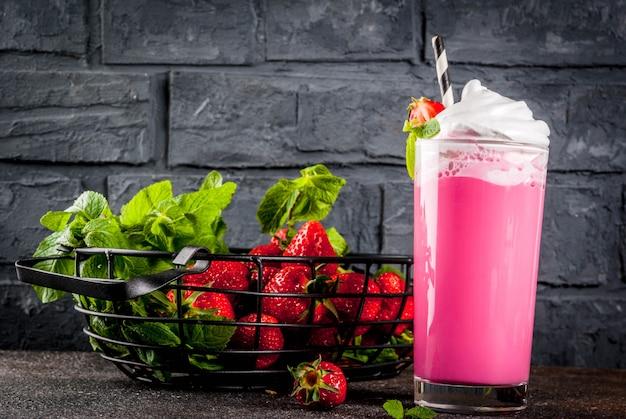 Milk-shake aux fraises froid avec des baies fraîches et de la menthe sur fond sombre