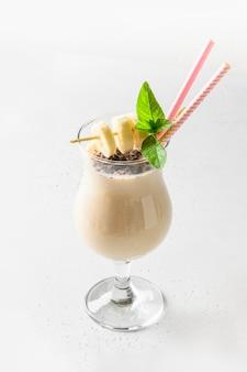 Milk-shake à la banane dans un verre à cocktail isolé sur blanc.