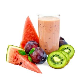 Milk-shake dans un bécher en verre avec prunes, kiwi et pastèque isolé sur fond blanc