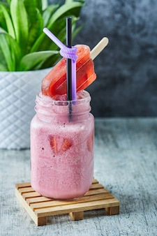 Milk-shake à la fraise et glace avec de la paille sur la surface en marbre