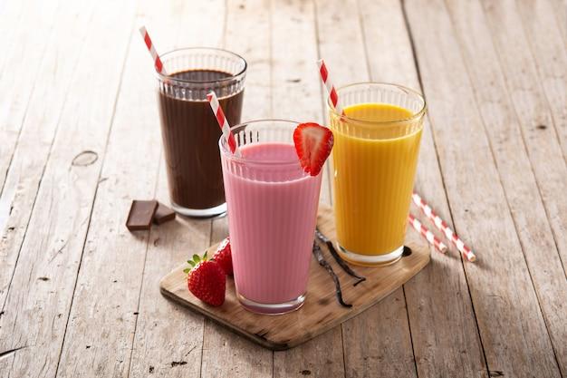 Milk-shakes au chocolat, fraises et vanille sur table en bois rustique