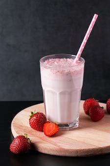 Milkshake frais aux fraises sur fond noir. boisson d'été avec une paille dans un verre. place pour le texte.
