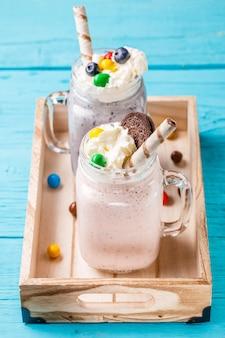Milkshakes aux fraises et aux bleuets frais sur la table bleue.