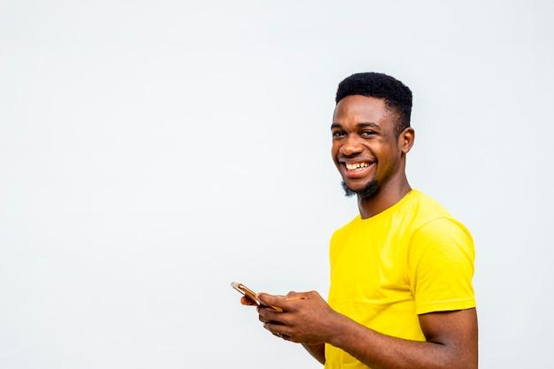 Le millénaire africain noir discute avec des amis sur les réseaux sociaux, lit les actualités en ligne. jeune étudiant universitaire payant des factures avec un téléphone portable