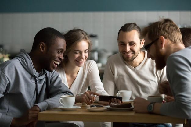 Millennial girl montrant une vidéo mobile amusante à des amis au café