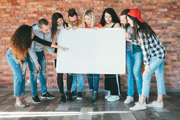 Millennials enthousiastes tenant une maquette de tableau blanc vierge.