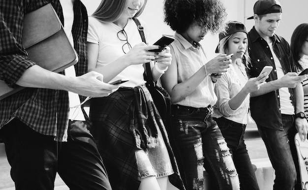 Millennials utilisant des smartphones ensemble à l'extérieur
