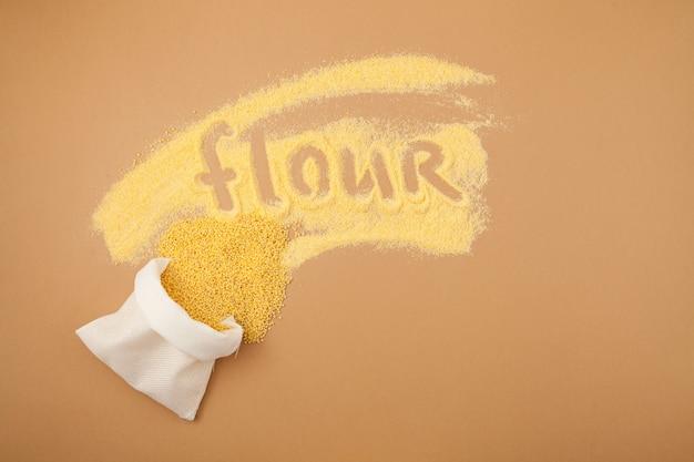 Le millet dans le sac blanc et la farine grossière organique sont dispersés sur le fond beige