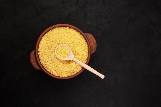 Millet décortiqué dans un pot en argile vue de dessus cuillère en bois à grain jaune espace de copie sur fond sombre