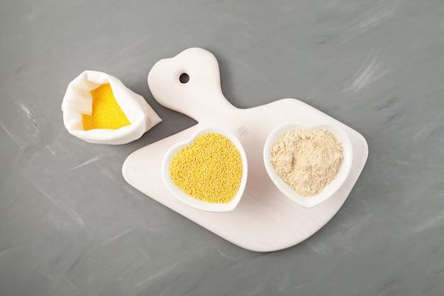 Millet décortiqué et farine grossière sur une planche à découper blanche vue de dessus fond gris grain jaune