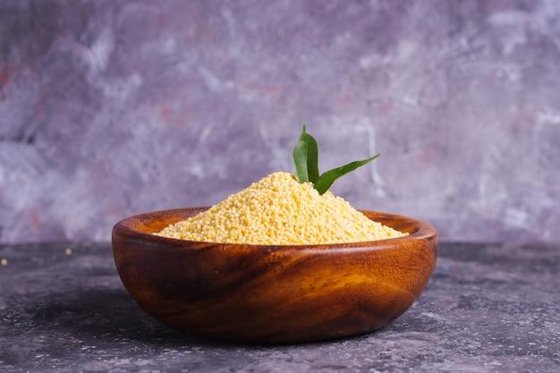 Millet jaune cru pour une bonne nutrition et santé dans une assiette en bois sur fond gris