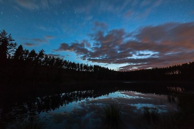 Un million d'étoiles sur le ciel nuageux au-dessus du lac la nuit