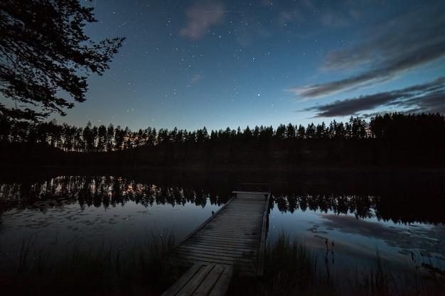 Un million d'étoiles sur le ciel nuageux au-dessus du lac pendant la nuit. pont au premier plan