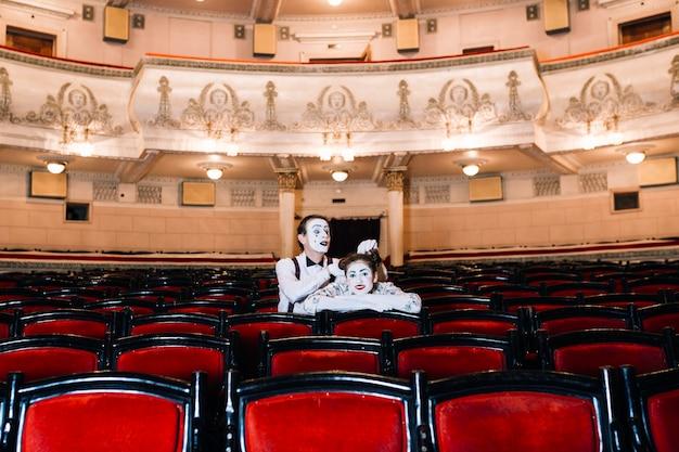 Mime artiste masculin jouant avec les cheveux de femme mime assis ensemble sur une chaise dans l'auditorium