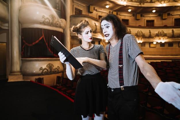 Mime féminin aidant le mime masculin tout en jouant sur scène