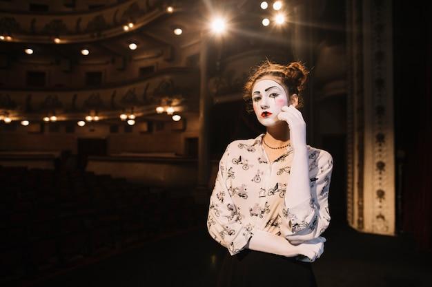 Mime féminin contemplé debout sur scène dans l'auditorium