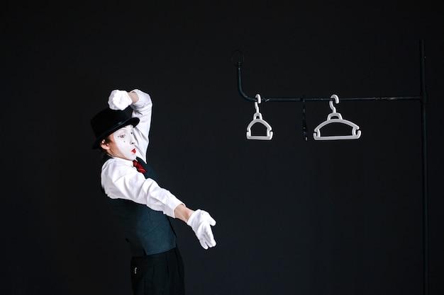 Mime se tient debout devant les chevilles pendues sur le bâton