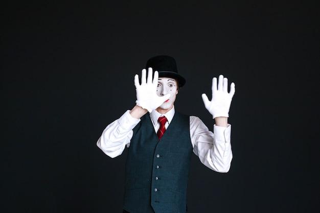 Mime tient la main sur un verre invisible