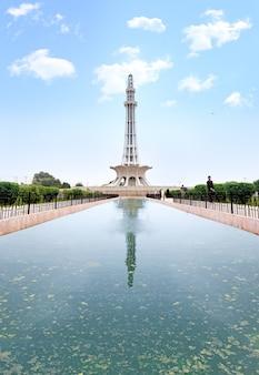 Minar e pakistan en été ciel de nuages avec la réflexion de l'eau pure