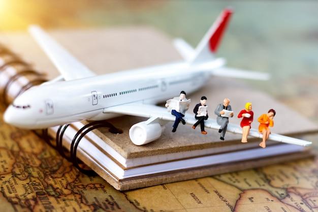 Minature people: voyager avec un livre de lecture dans l'avion.